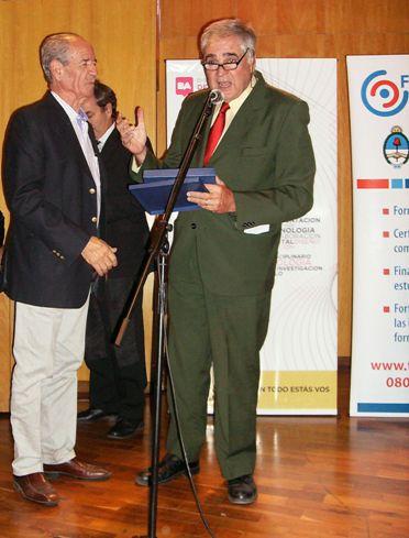 Sr. Roberto Campi (izq) de la firma Expocolor recibiendo la placa de reconocimiento de mandos de Juan Garat.